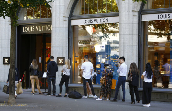 People queue in front of a shop of French luxury fashion brand Louis Vuitton in Zurich