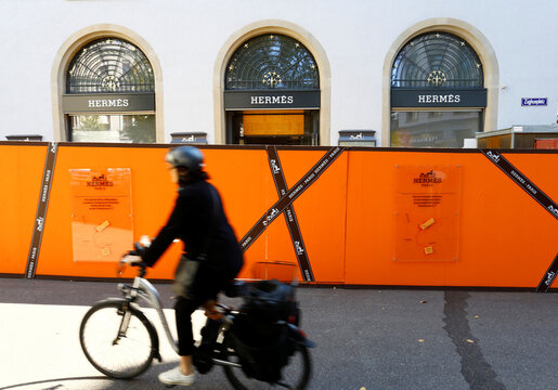 Woman cycles past a shop of French luxury fashion brand Hermes in Zurich