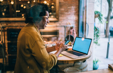 Cheerful male freelancer browsing smartphone sitting in cafe with laptop