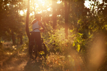 Morning dawn cycling workout. Riding in the woods in nature in the rays of dawn.