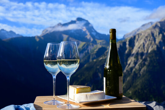 Tasty cheese and wine from Savoy region in France,  tomme and reblochon de savoie cheeses and glass of white wine served outdoor with Alpine mountains peaks on background