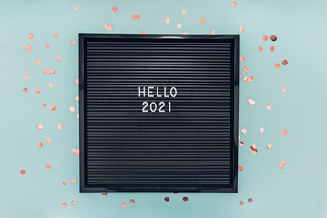 Numbers 2021 on letterboard on blue background with glitter confetti.