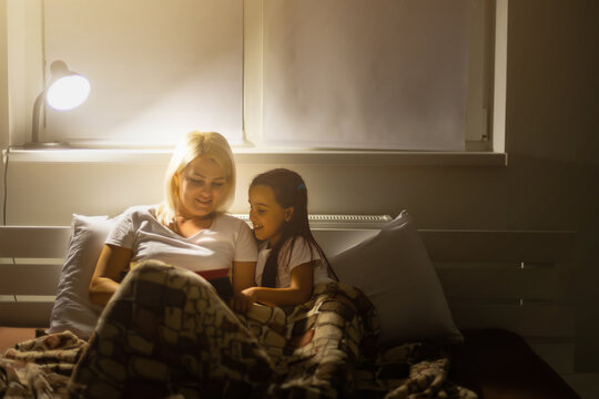 Family bedtime. Mom and child daughter reading a book in bed
