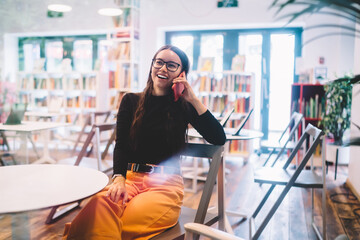 Happy Caucasian woman in classic glasses for provide eyes protection laughing during friendly smartphone conversation with university colleague, cheerful student calling via cellphone device