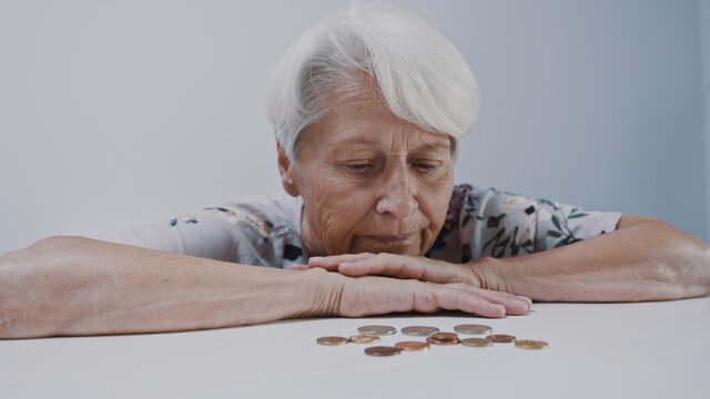 Sad face expression of old gray haired woman looking in few coins left on the table. High quality photo