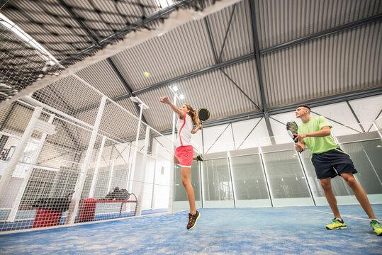 paddle tennis indoors training, woman hits ball