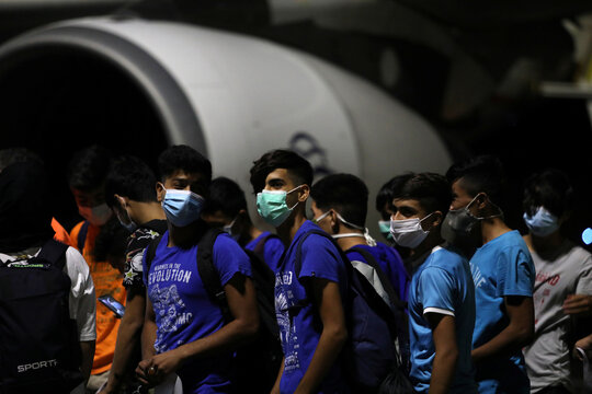 Unaccompanied refugee minors board a plane to the mainland following a fire at the Moria camp for refugees and migrants on the island of Lesbos