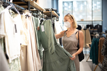 Fashionable woman wearing protective face mask shopping clothes in reopen retail shopping store....