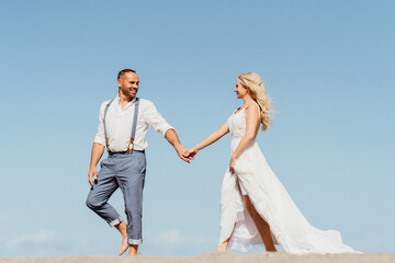 Happy couple running on the beach holding hands. Beach sand and blue sky with free copy space