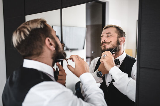 Young man trims his beard with scissors while standing in front of a mirror