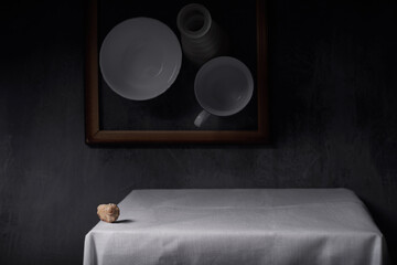 Still life with a shell on a table covered with a white tablecloth.