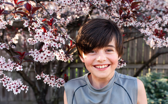 Portrait of happy young boy in front of flowering trees in a garden.