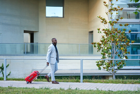 African-American in a white suit and a red suitcase.