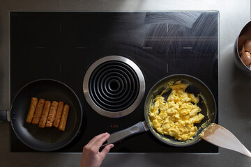 Overhead view of someone cooking scrambled eggs and sausage