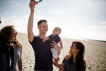 Dad Holding up Sunglasses to get Son's Attention While Family Smiles