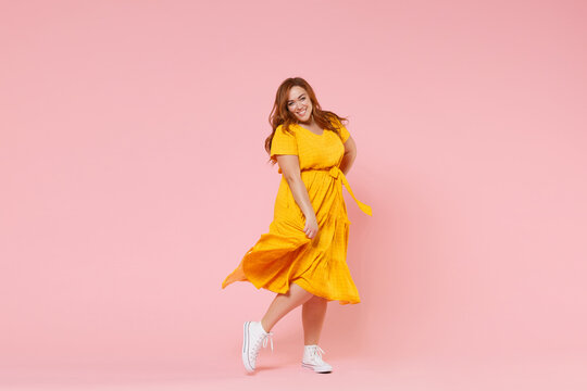 Full length portrait of smiling beautiful charming young redhead plus size body positive female woman girl 20s in yellow dress posing looking camera isolated on pastel pink color background studio.