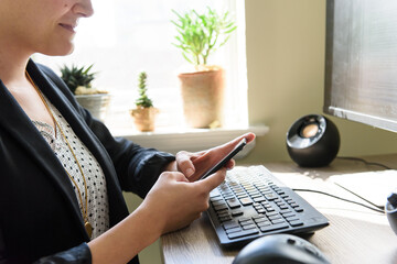 Close up of young business woman hands texting at home office