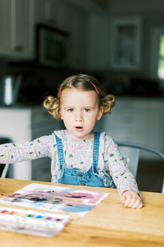 A little girl painting with watercolors at a table