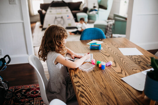 Young girl coloring picture while sitting at dining room table