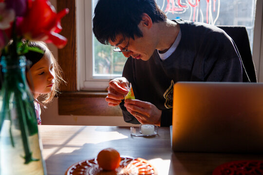 A father helps his child with a paper craft while she watches closely