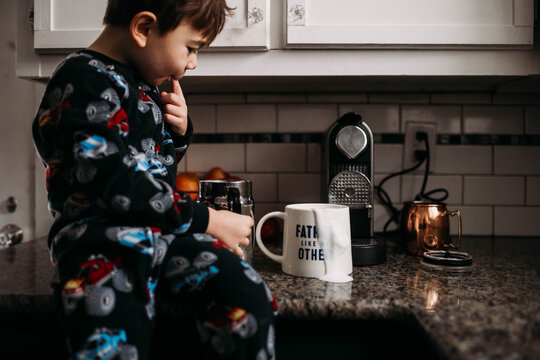 Boy sitting on countertop with spilled milk on coffee cup