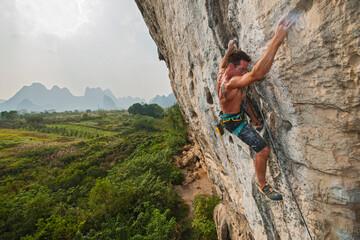 man climbing rock face in Yangshuo / China