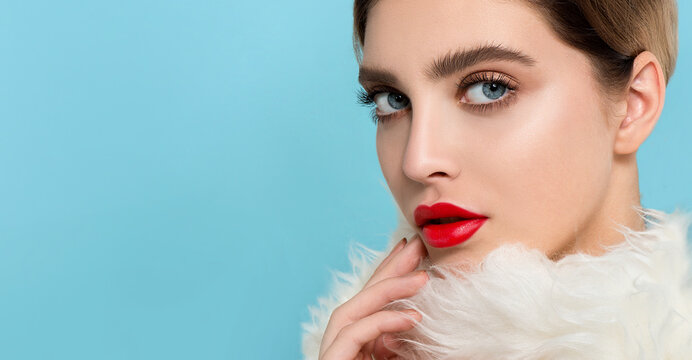 Portrait of beautiful young woman wearing red clothes with perfect young skin, red matt lips and nails.