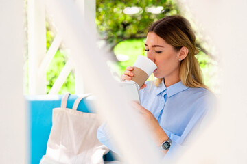 Beautiful Woman Drinking Coffee From Coffee Recyclable Cardboard Takeaway Cup at Street Cafe and Sitting Near Cotton Eco Friendly Bag. Mug and Bag With Copy Space