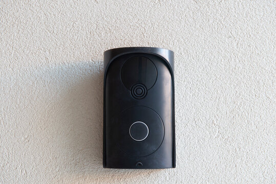 Black intercom without camera on rough beige wall.