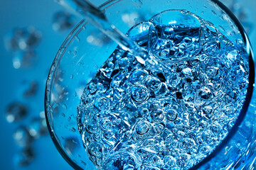 Mineral water is poured into a glass.