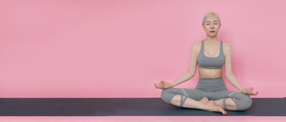 Female yoga instructor sitting in lotus position and meditation on pink background. Women wearing fashionable sportswear practicing yoga in class. Well being, wellness and fitness center concept.