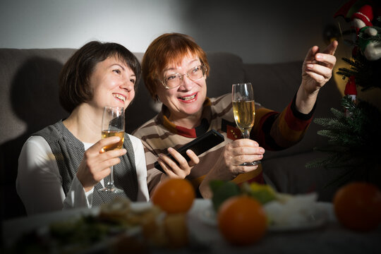 Happy mother and daughter drink champagne and watch TV on Christmas night. High quality photo