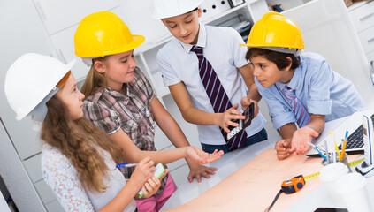 Group of children in helmet talking about building near laptop