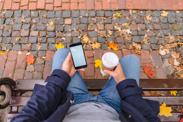 no face man sitting on the bench at city park drinking coffee surfing on phone