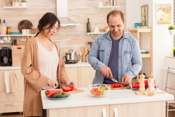 Young couple cutting tomatoes for salad in kitchen using cutting board. Happy in love cheerful and carefree couple helping each other to prepare meal