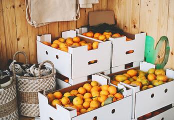 Cardboard boxes of organic tangerines in zero waste shop.