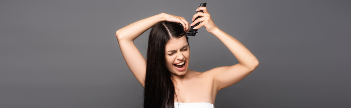 brunette long haired woman shaving head with electric razor and screaming isolated on black, panoramic shot