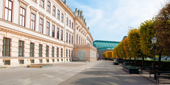vienna, austria - OCT 17, 2019: terrace on the backside of albertina museum building. cafe and restaurant place. benches under the trees in fall foliage. sunny afternoon