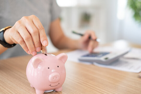 savings and finance. women put coin into the piggy bank