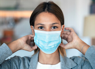 Young beautiful woman wearing an hygienic mask to prevent others from a virus while looking at camera in the home.