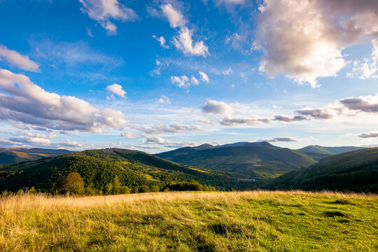 rural landscape in mountains at sunset. grassy pasture on the hill in evening light. high mountains in the distance. beautiful clouds on the blue sky. wonderful early autumn scenery