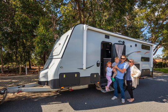 A Young Family proudly standing outside of their  caravan in front of a Park
