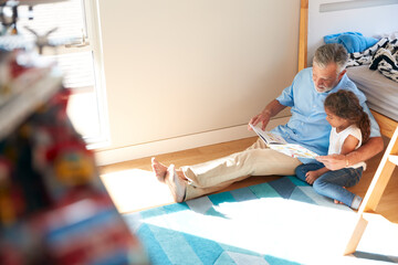 Hispanic Grandfather And Granddaughter Sitting On Floor Of Childrens Bedroom Reading Book Together