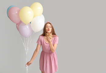 Photo sur Plexiglas Pain Young woman with balloons and birthday cake on grey background