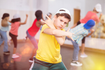 Cheerful preteen girls and boys hip hop dancers doing dance workout with female trainer during group class