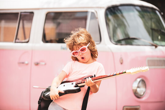 Child musician playing the guitar like a rockstar on pink background in neon light. Caucasian little boy learning to play guitar.