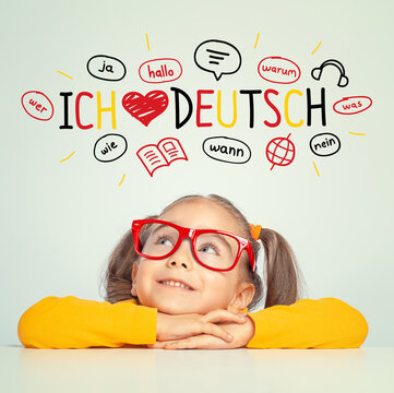 Beautiful cute little girl with eyeglasses looking at ich liebe deutch text and illustrations. English: i love german.  Foreign language learning concept.