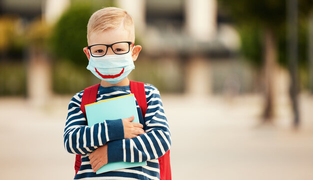 Little schoolboy in protective mask and eyeglasses.