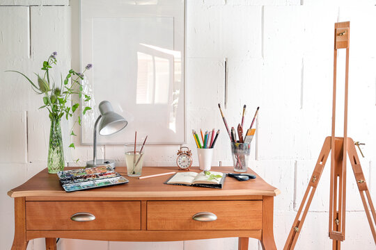 Creative place for art work or hobby, crayons, sketchbook, watercolor and brushes on a small wooden desk and an empty easel against a white painted wall