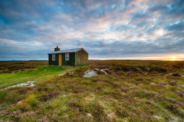 Wall Mural - Dramatic sky over an old Shieling hut on moorland near Stornoway